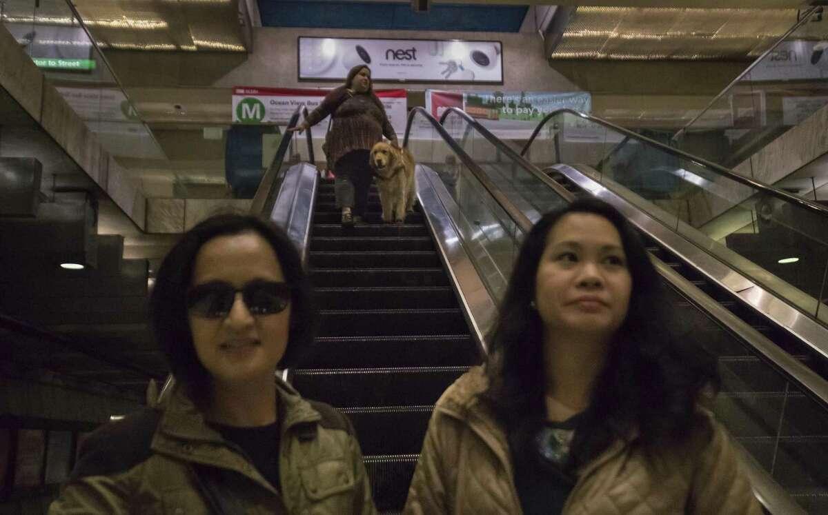 Maia Scott and Fiddler ride an escalator behind Cecille Matias and Caroline Cruz at a Muni Metro station in San Francisco. Fiddler is Scott's third service dog.