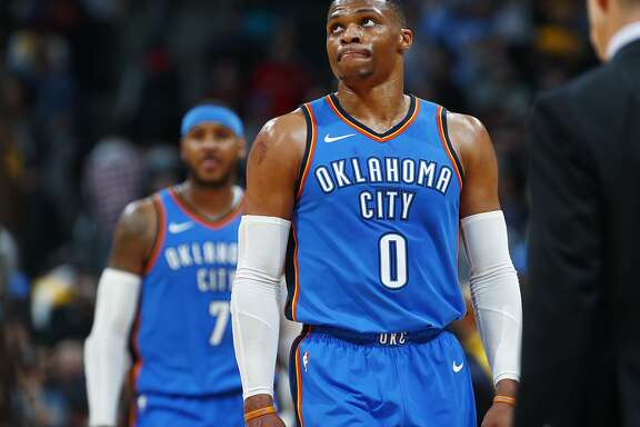 Oklahoma City Thunder guard Russell Westbrook, front, and forward Carmelo Anthony head off the court as time runs out in the second half of an NBA basketball game against the Denver Nuggets late Thursday, Nov. 9, 2017, in Denver. The Nuggets won 102-94. (AP Photo/David Zalubowski)