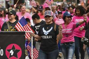 Members of the Women's Veteran's of San Antonio wave their flags while marching in Saturday's Veteran's Day Parade along Houston St.