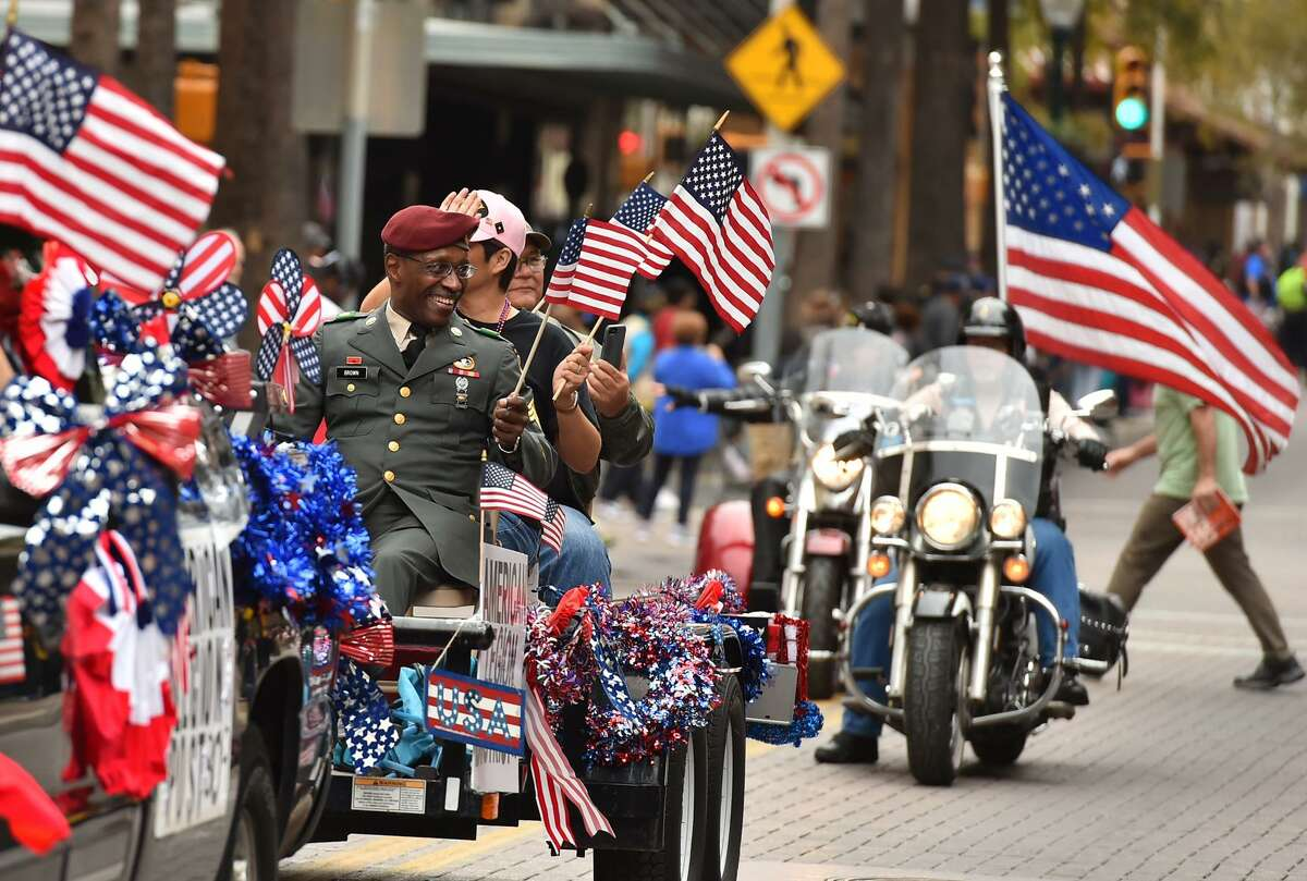 Members of the American Legion Post 309 wave flags while riding along Houston St. during the Veteran's Day Parade Saturday.