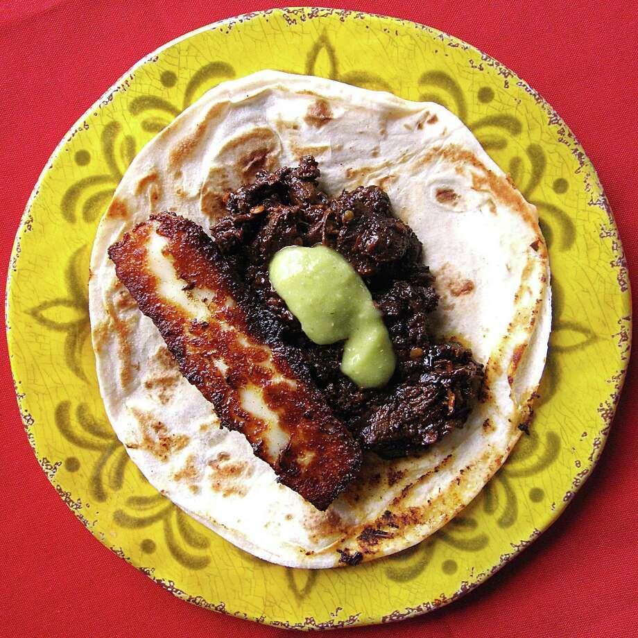 Rib-eye en chile pasilla taco with fried panela cheese on a handmade flour tortilla from Viva Villa Taquería. Photo: Mike Sutter /San Antonio Express-News