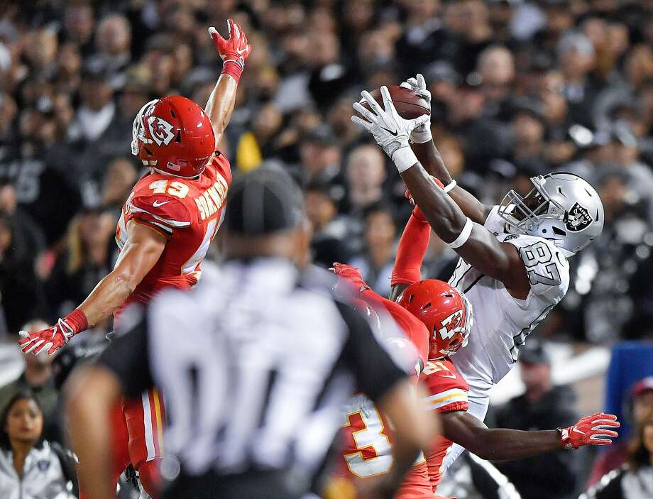 Oakland Raiders tight end Jared Cook catches a 29-yard pass to the one-yard line over the Kansas City Chiefs defense in the closing seconds of the fourth quarter during the football game Thursday, Oct. 19, 2017 against the Kansas City Chiefs at Oakland-Alameda County Coliseum in Oakland, Calif. The Raiders won 31-30. (John Sleezer/Kansas City Star/TNS) Photo: John Sleezer, TNS