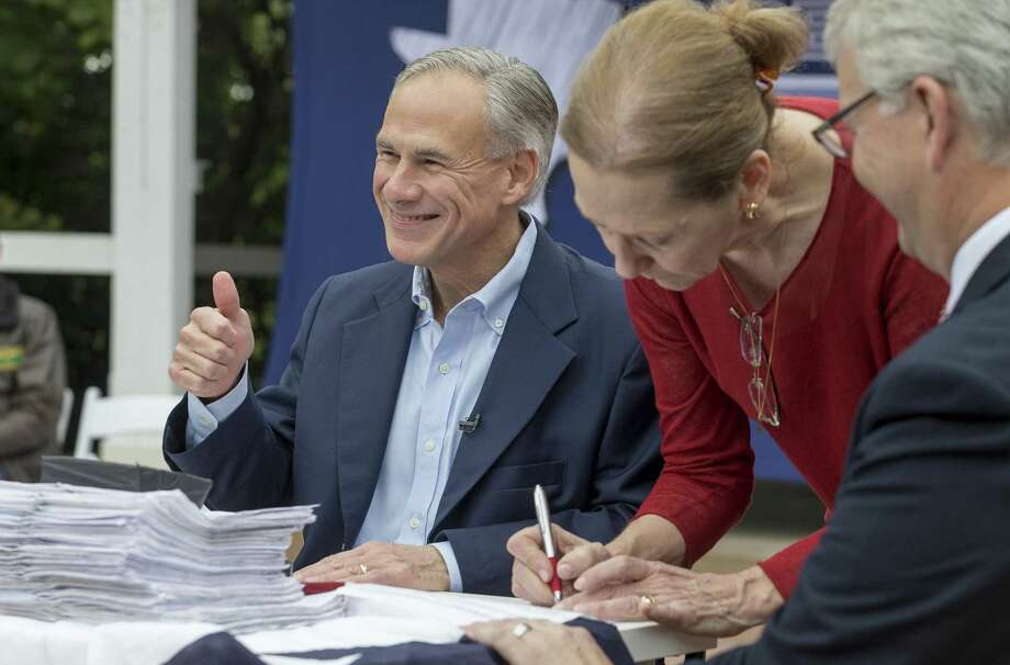 Gov. Greg Abbott signs paperwork with notary public Mary Eichner and State Republican Party Chairman James Dickey during a picnic celebrating his reelection filing day announcement at The American Legion- Charles Johnson House in Austin Saturday, Nov. 11, 2017. (Stephen Spillman / for Express-News) Photo: Stephen Spillman / Stephen Spillman / stephenspillman@me.com Stephen Spillman