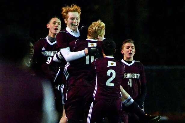Farmington's Nate Hughes, facing camera, celebrates a goal against Shelton with teammates during Class LL boys soccer state tournament action in Shelton, Conn., on Saturday Nov. 11, 2017.