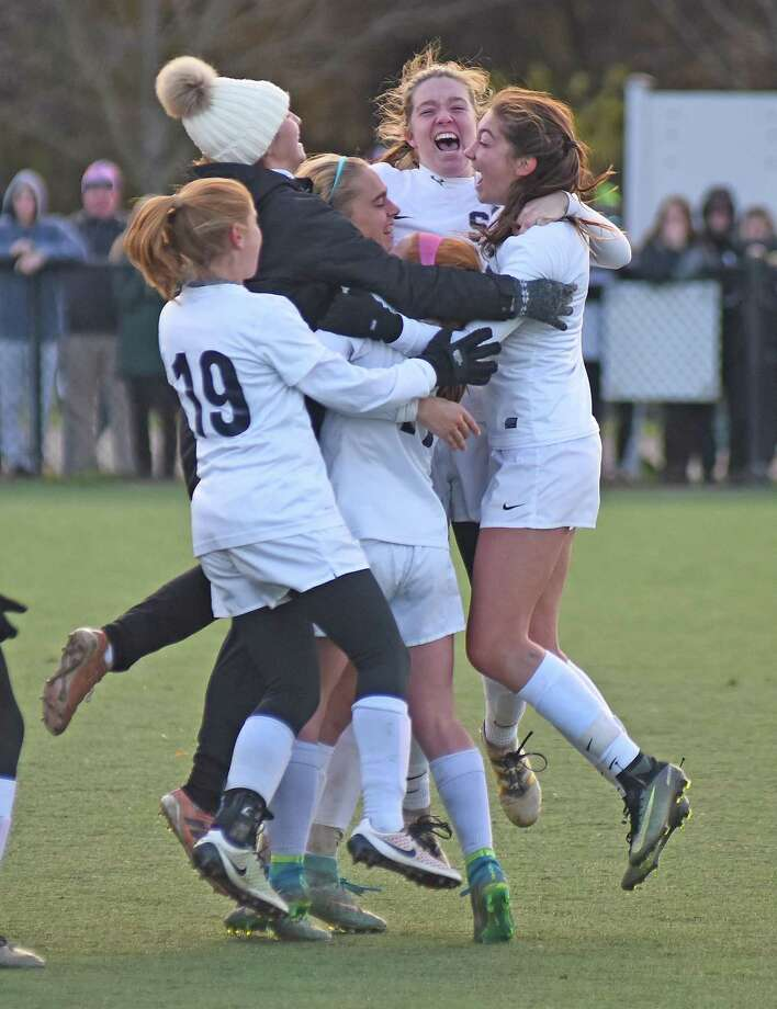 The Staples girls soccer team converges on Ashley Wright, center, after she clinched Saturday's CIAC Class LL girls soccer quarterfinal with a penalty kick in the Wreckers' 2-1 (3-1 PK) win over Trumbull. Photo: John Nash/Hearst Media Connecticut