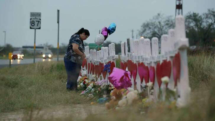 A woman visits a makeshift memorial on Nov. 10 along the highway for the victims of the church shooting at Sutherland Springs Baptist Church in Sutherland Springs, Texas. A man opened fire inside the church in the small South Texas community on Sunday, Nov. 5, killing more than two dozen. (AP Photo/Eric Gay)