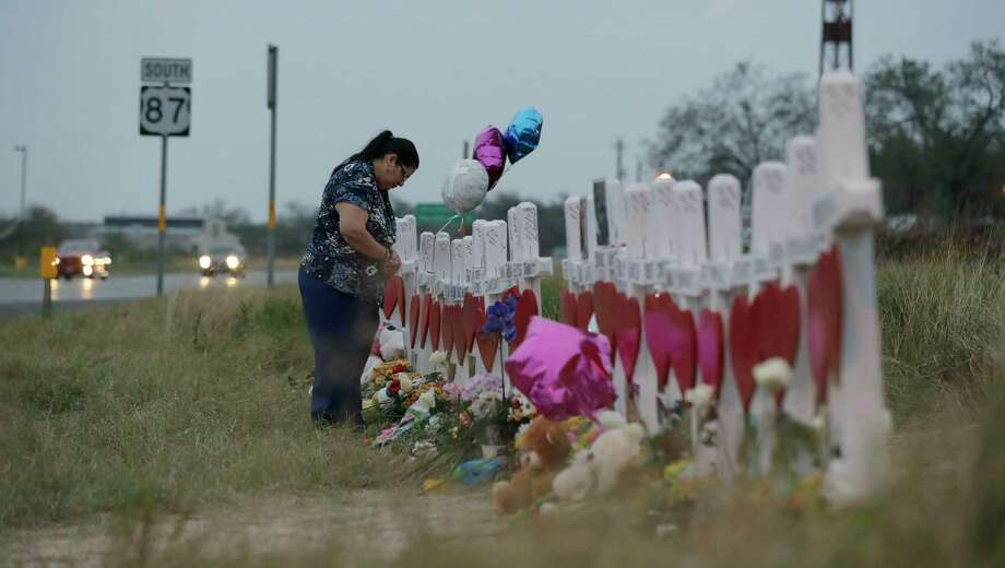 A woman visits a makeshift memorial on Nov. 10 along the highway for the victims of the church shooting at Sutherland Springs Baptist Church in Sutherland Springs, Texas. A man opened fire inside the church in the small South Texas community on Sunday, Nov. 5, killing more than two dozen. (AP Photo/Eric Gay) Photo: Eric Gay, STF / Copyright 2017 The Associated Press. All rights reserved.