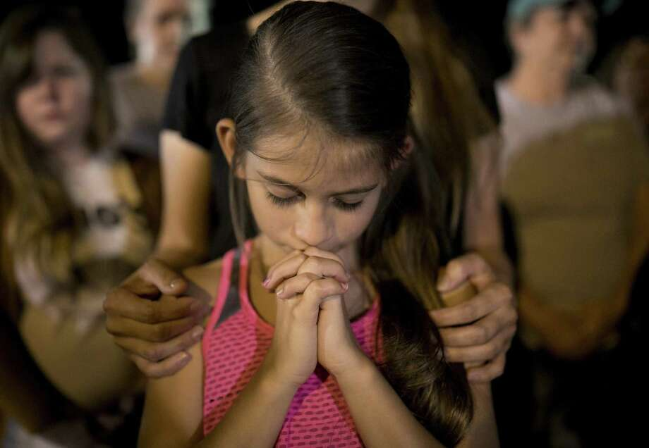 Sophia Martinez, 9, prays at a memorial service for the victims of Sunday's church shooting in Sutherland Springs, Texas, Monday, Nov. 6, 2017. The gunman of the deadly shooting had a history of domestic violence and sent threatening text messages to his mother-in-law, a member of First Baptist, before the attack in which he fired at least 450 rounds at helpless worshippers, authorities said Monday. (Jay Janner/Austin American-Statesman via AP) Photo: Jay Janner, MBO / Associated Press / Austin American-Statesman