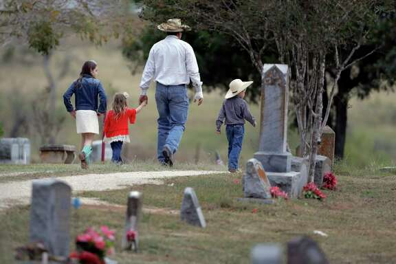 A family arrives for a grave-side service for Richard and Therese Rodriguez at the Sutherland Springs Cemetery Saturday.