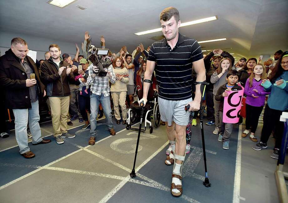 All-American distance runner Collin Walsh, 32, of North Haven crosses the finish-line, surrounded by family, friends, alumni athletes and former teammates during the 55-meter dash at the Southern Connecticut State University alumni track meet, Saturday, Nov. 11, 2017, at Moore Field House in New Haven. Walsh is battling multiple sclerosis, a disease that attacked his body leaving him 80 percent paralyzed a year and a half ago. Photo: Catherine Avalone / Hearst Connecticut Media / New Haven Register