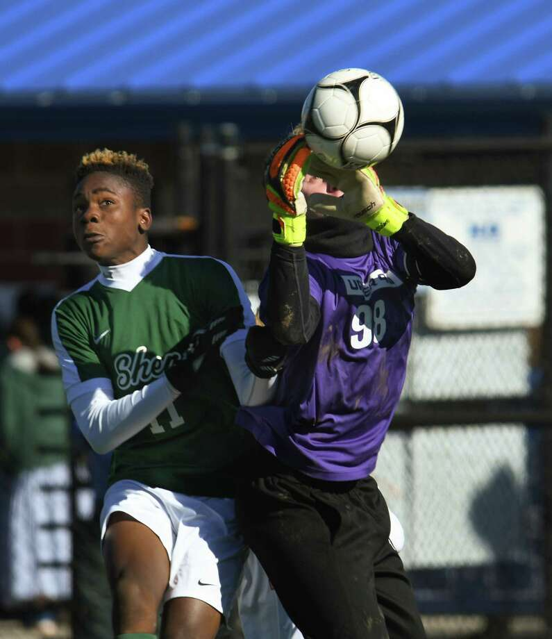 Shen's Jaylin Sykes jumps with the Hills West goalkeeper as he makes a save during the Class AA soccer state semifinal on Saturday in Middletown. Shen fell to Hills West following two overtime periods in a final shootout. (Jenn March/Special to the Times Union) Photo: Jenn March / 000000000