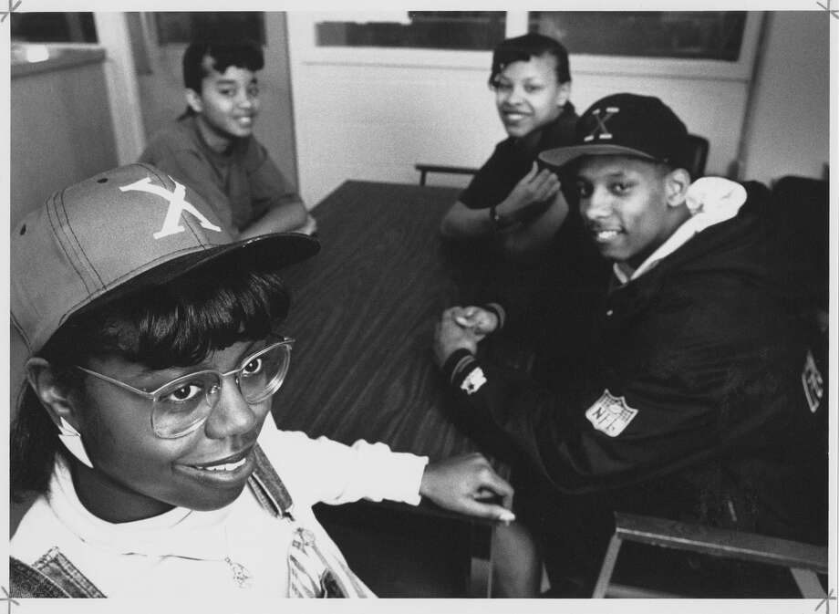 """Rainier Beach High School students Deltrinee Owens, left, and Domico Curry, right, wear """"X"""" hats as they sit with friends Tianna Scott and Ruthetta Lee. The hats were popular tie-ins to film director Spike Lee's biopic """"Malcolm X"""" released on November, 18, 1992. Photo: MOHAI, Seattle Post-Intelligencer Photograph Collection, 2000.107.60.35.02"""