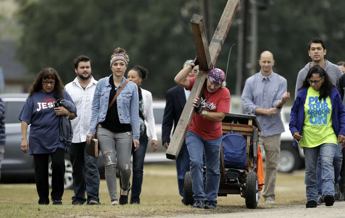 Stephen Hope carries a cross as he and other leave after a worship service for the victims of the shooting at Sutherland Springs Baptist Church, Sunday, Nov. 12, 2017, in Sutherland Springs, Texas, a week after a man opened fire inside the church. Church members will gather this week in a large tent set up at a baseball park. (AP Photo/Eric Gay)
