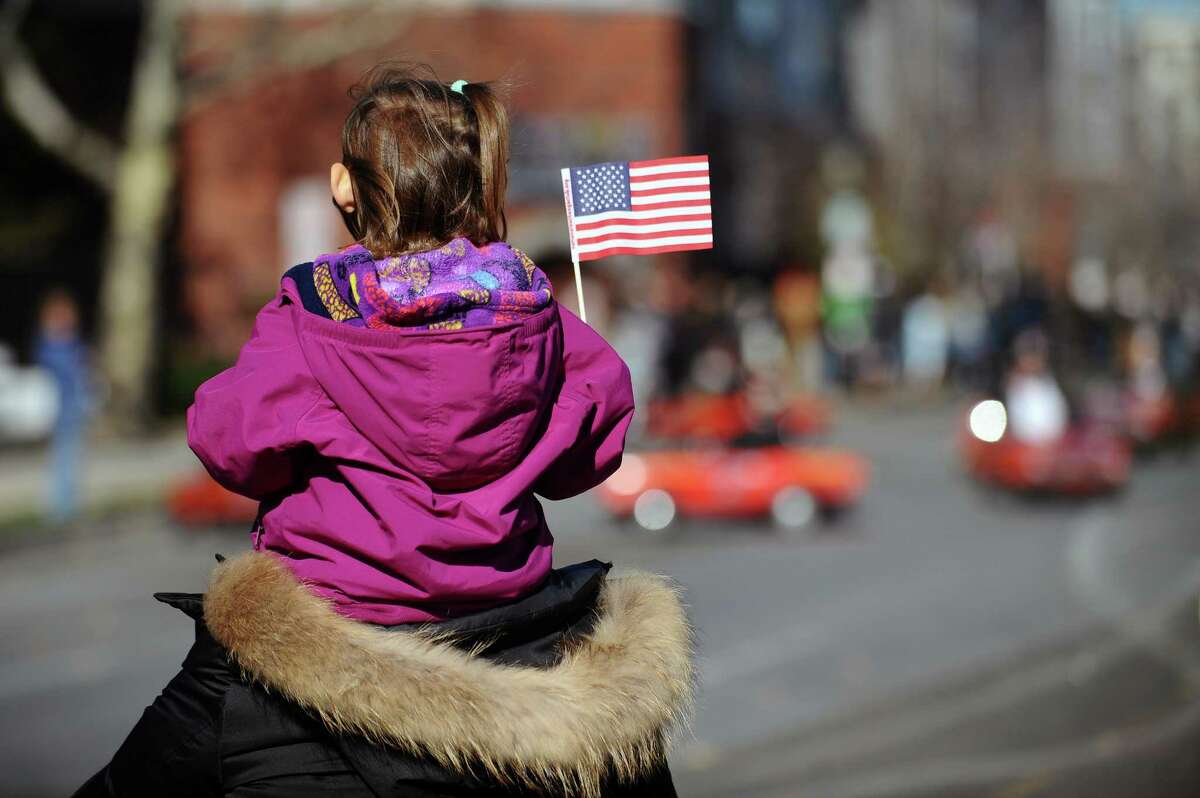 Two-year-old Penelope Soltes sits on the shoulders of her aunt Catherine Soltes while waving her American flag and watching the annual Veterans Day Parade walk down Bedford Street in downtown Stamford, Conn. on Sunday, Nov. 12, 2017.