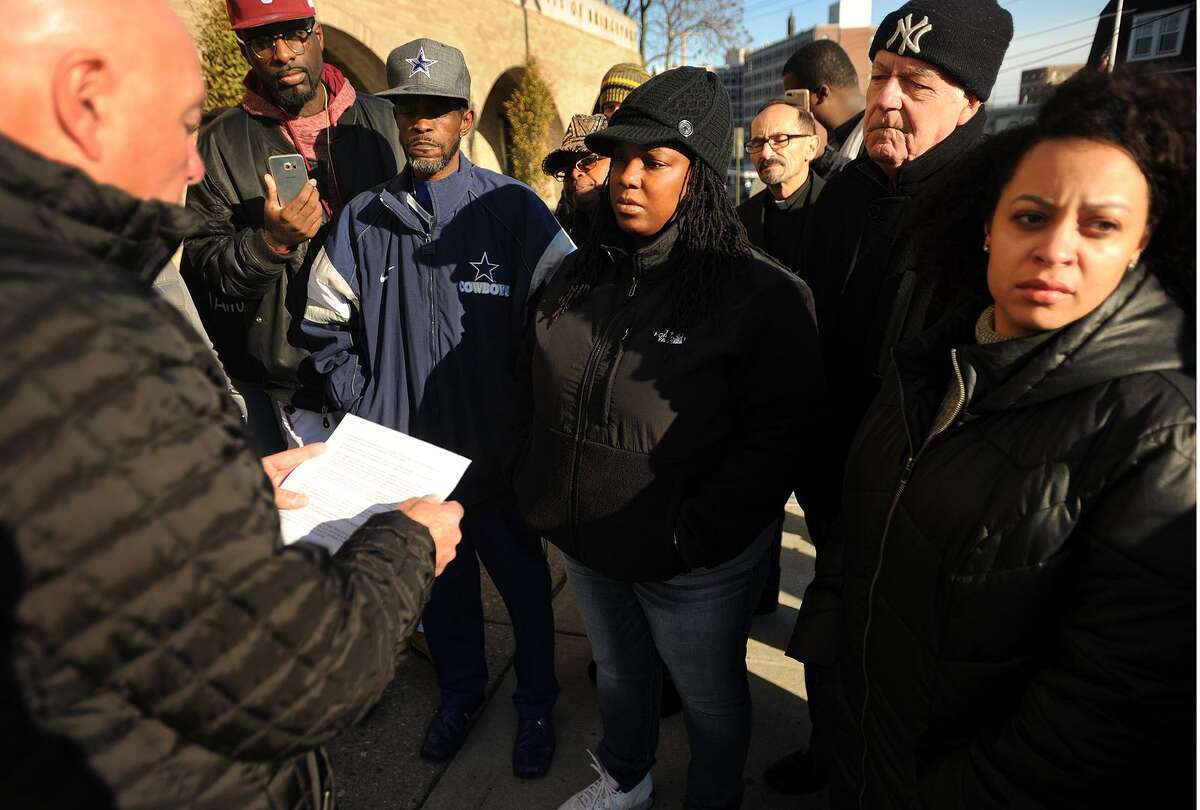 Bridgeport Police Chief A.J. Perez, left, reads a statement to protesters outside Police Headquarters on Sunday regarding an impending investigation into the incident Friday night between police and city resident Aaron Kearney. Kearney's family members, including his aunt, Tiffany Elliott, center, and sister Antionette Rogers, right, called for quick action for an officer they say repeatedly punched Kearney in the head while he was being held down by other officers.