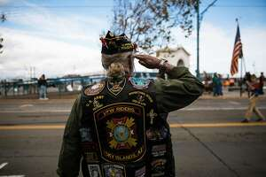 Mike Edmond, a retired police officer and a former U.S. Army soldier, salutes the American Flag during the Veterans Day Parade in San Francisco, Calif. Sunday, November 12, 2017.