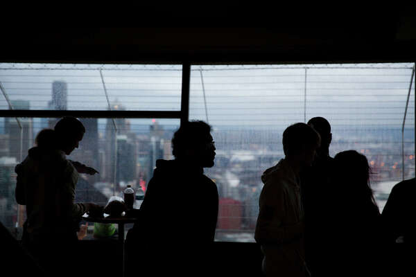 Tourists mill about in the observation deck of the Space Needle, Thursday, Nov. 9, 2017. The interior and exterior of the deck are being renovated sections at a time so it can remain open to the public through construction.