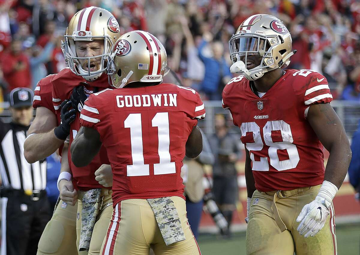 San Francisco 49ers quarterback C.J. Beathard, left, is congratulated by wide receiver Marquise Goodwin (11) and running back Carlos Hyde (28) after scoring a touchdown against the New York Giants during the second half of an NFL football game in Santa Clara, Calif., Sunday, Nov. 12, 2017. (AP Photo/Marcio Jose Sanchez)