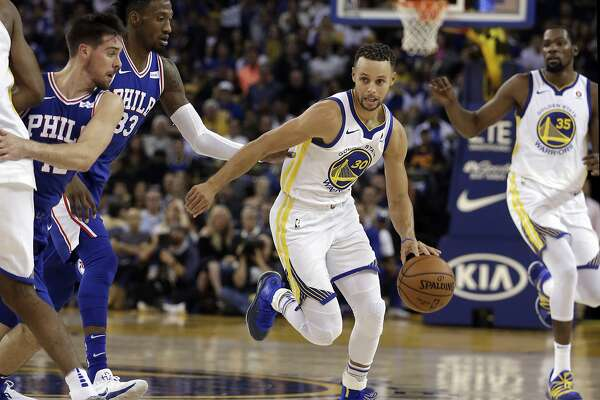 Golden State Warriors' Stephen Curry, center, drives the ball away from Philadelphia 76ers' T.J. McConnell, left, and Robert Covington (33) during the first half of an NBA basketball game Saturday, Nov. 11, 2017, in Oakland, Calif. The Warriors won 135-114. (AP Photo/Ben Margot)