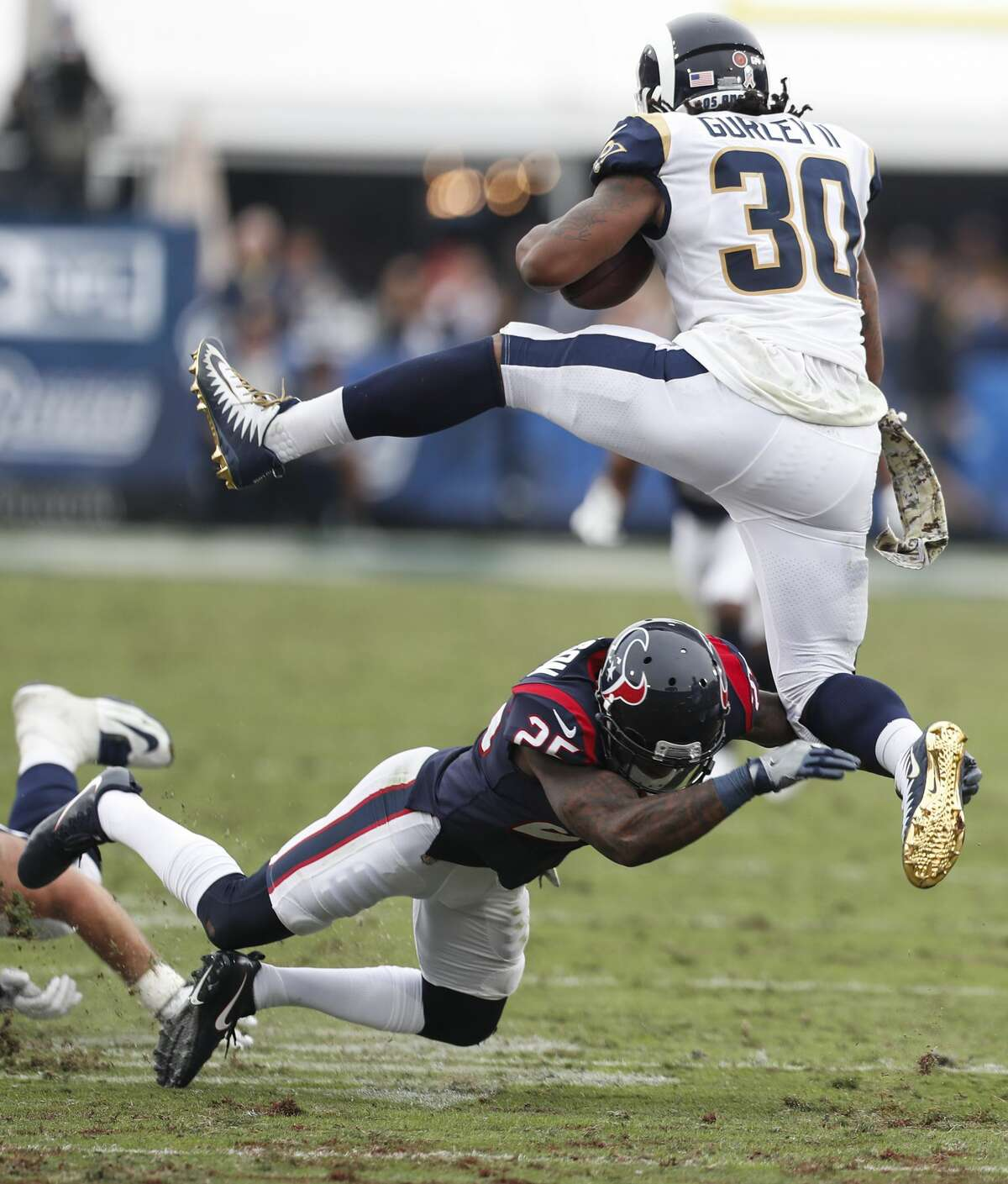 Los Angeles Rams running back Todd Gurley (30) leaps over Houston Texans cornerback Kareem Jackson (25) during the third quarter of an NFL football game at the Los Angeles Memorial Coliseum on Sunday, Nov. 12, 2017, in Los Angeles. ( Brett Coomer / Houston Chronicle )