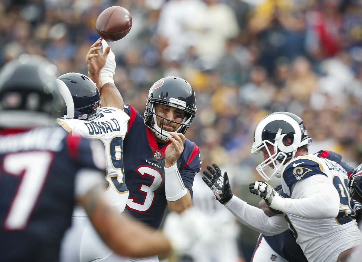 Houston Texans quarterback Tom Savage (3) has the ball knocked out of his hand by Los Angeles Rams defensive end Aaron Donald (99) during the second quarter of an NFL football game at the Los Angeles Memorial Coliseum on Sunday, Nov. 12, 2017, in Los Angeles. ( Brett Coomer / Houston Chronicle )
