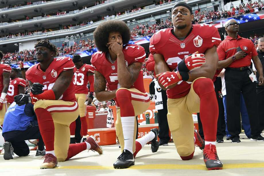 Eli Harold (left), Colin Kaepernick and Eric Reid take a knee during the national anthem before a 2016 game to protest police violence against African Americans, part of a protest that continues this season despite having cost Kaepernick his NFL career. Photo: Thearon W. Henderson / Getty Images / 2016 Getty Images