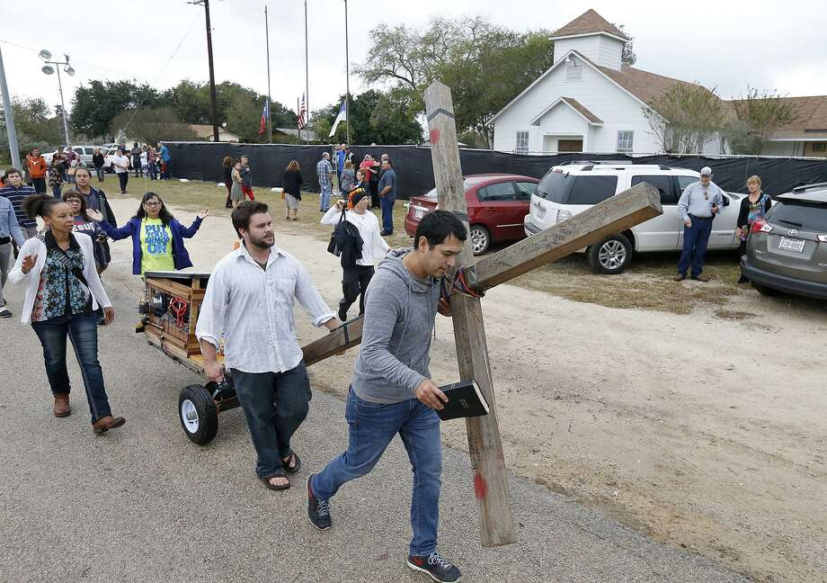 Members of the San Antonio Tabernacle House of Prayer pull a cross past the First Baptist Church of Sutherland Springs, where 26 people were killed during a Sunday service. A reader says media outlets should refrain from identifying the perpetrators of such massacres. Photo: Edward A. Ornelas /San Antonio Express-News / © 2017 San Antonio Express-News
