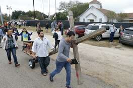 Members of the San Antonio Tabernacle House of Prayer pull a cross past the First Baptist Church of Sutherland Springs, where 26 people were killed during a Sunday service. A reader says media outlets should refrain from identifying the perpetrators of such massacres.