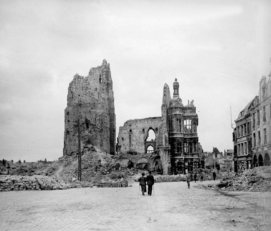 The town hall and the belfry of Arras in ruins, seen from the main square in 1914; and the same scene at Place des Heros in 2014. Photo: Roger Viollet/Roger Viollet/Getty Images