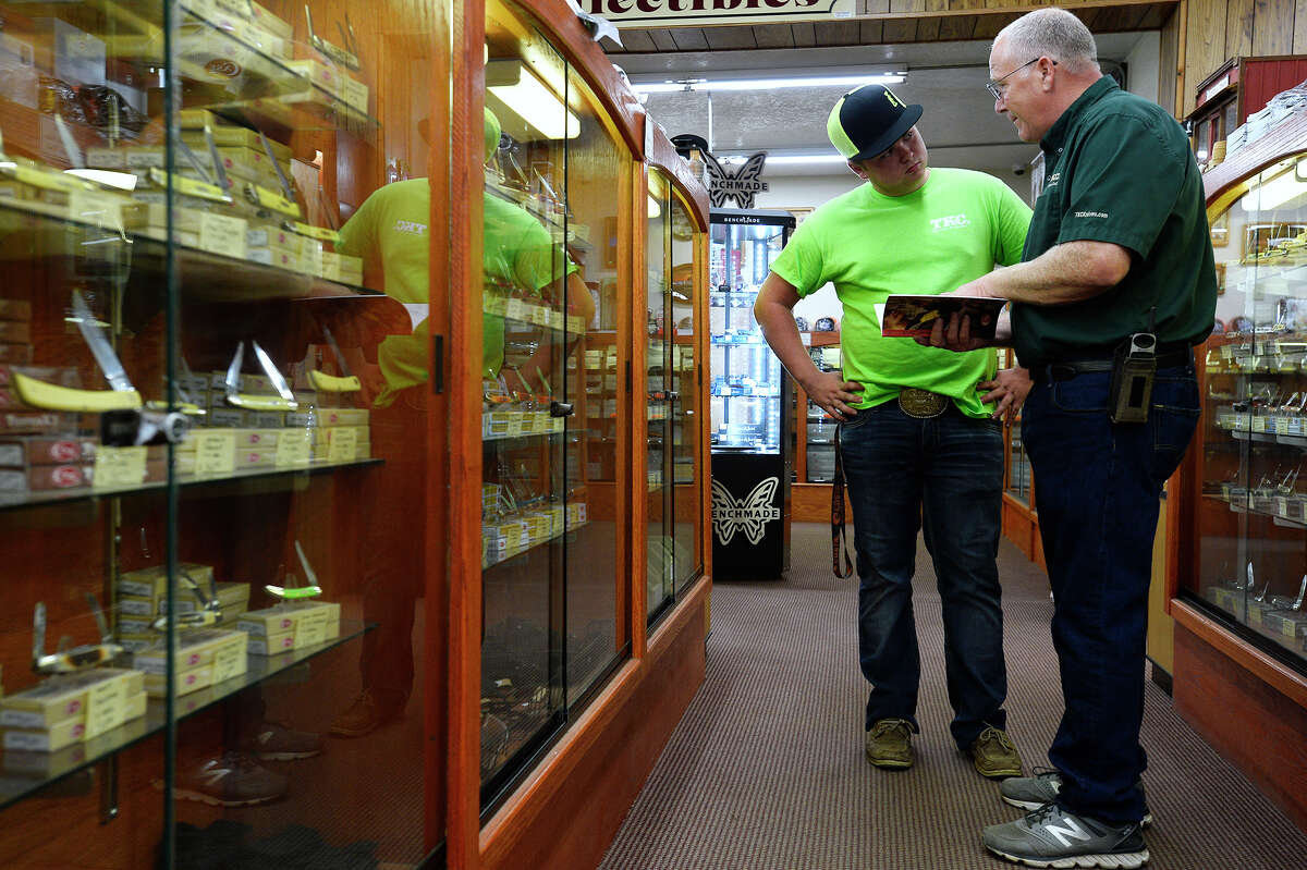 Marvin Mott talks with employee Dalton Holley at Texas Knives and Collectibles in Spurger. The shop's large inventory of knives resulted in Spurger being named the Knife Capital of Texas. Photo taken Friday 11/3/17 Ryan Pelham/The Enterprise