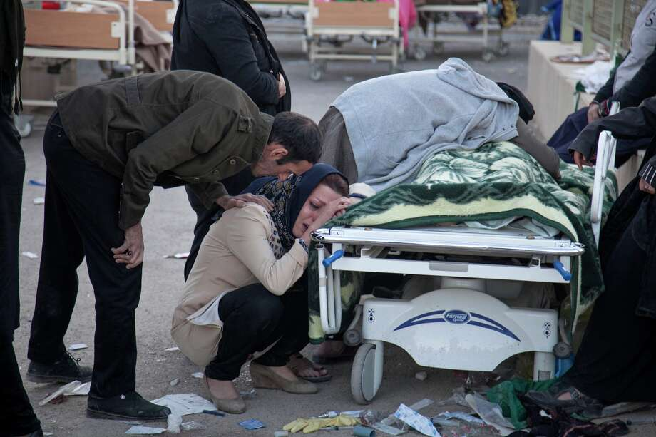 In this photo provided by Tasnim News Agency, relatives weep over the body of a victim of the earthquake at Sarpol-e-Zahab town in western Iran, Monday, Nov. 13, 2017. A powerful 7.3 magnitude earthquake that struck the Iraq-Iran border region killed more than three hundreds people in both countries, sent people fleeing their homes into the night and was felt as far west as the Mediterranean coast, authorities reported on Monday. Photo: Farzad Menati/Tasnim News Agency Via AP