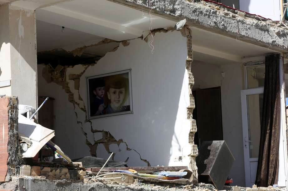 A framed picture of a boy hung on a wall inside a partially collapsed building is seen in Sarpol-e Zahab town of Kermanshah, Iran on November 13, 2017 following a 7.3 magnitude earthquake that hit the Iraq and Iran. An earthquake measuring 7.3 on the Richter scale rocked northern Iraq and Iran, the U.S. Geological Survey said on Sunday evening. Turkish paramedic teams and rescue teams dispatched to the disaster area under the coordination of Turkish aid agencies; AFAD (Turkey's Disaster Management Agency) and Kizilay (Turkish Red Crescent). At least 211 died and 2,504 others were injured in Iran's bordering regions, especially in Kermanshah province in west. Photo: Fatemeh Bahrami/Anadolu Agency/Getty Images)