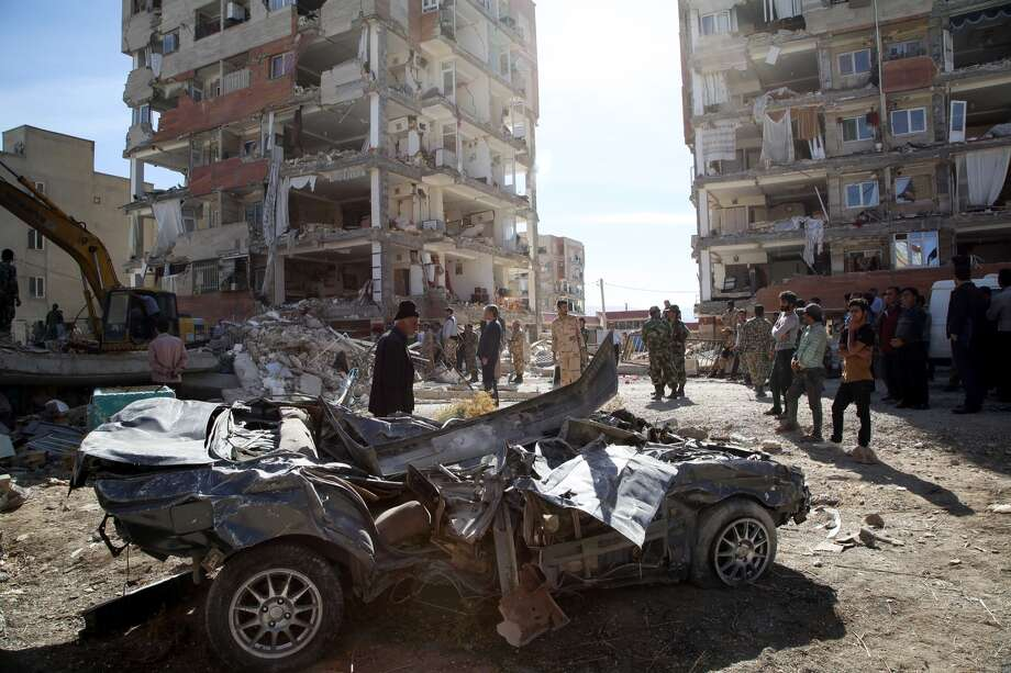 People inspect the debris of buildings and a destroyed vehicle at Sarpol-e Zahab province of Kermanshah, Iran on November 13, 2017 following a 7.3 magnitude earthquake that hit the Iraq and Iran. An earthquake measuring 7.3 on the Richter scale rocked northern Iraq and Iran, the U.S. Geological Survey said on Sunday evening. At least 341 died and 5,953 others were injured in Iran's bordering regions, especially in Kermanshah province in west. Photo: Fatemeh Bahrami/Anadolu Agency/Getty Images