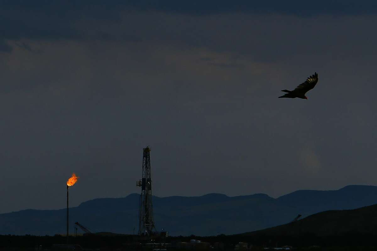 A vulture soars over an Apache Corporation flare and drilling rig north of the Davis Mountains Friday, Sept. 16, 2016 in Balmorhea, TX. Apache Corp. gifted $257,000 to the University of Texas' McDonald Observatory to help with the prevention of light pollution in dark West Texas skies - which are often used for research.
