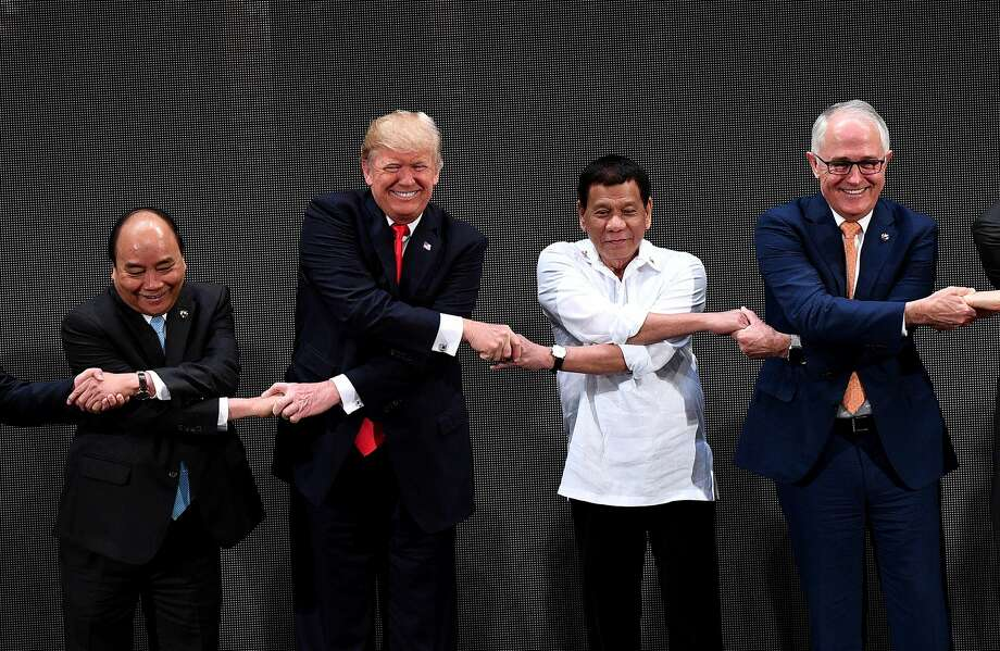 (L-R) The Association of Southeast Asian Nations (ASEAN) members Vietnam's Prime Minister Nguyen Xuan Phuc, US President Donald Trump, Philippine President Rodrigo Duterte, Australia Prime Minister Malcolm Turnbull, link hands during the Opening ceremony of the 31st ASEAN Summit in Cultural Center of the Philippines (CCP) in Manila on November 13, 2017. World leaders are in the Philippines' capital for two days of summits.   Photo: NOEL CELIS/AFP/Getty Images