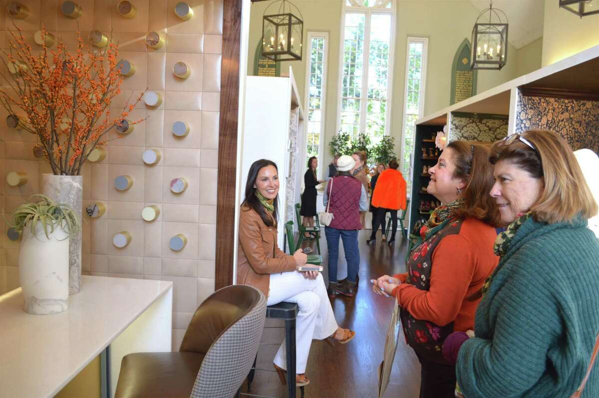 Christina Lake of Fairfield-based Forehand & Lake design watches Barbra Utting, center, and Roseanna Mihalick, both of Westport, admire her work at the Rooms with a View design show at Southport Congregational Church, Friday, Nov. 10, 2017, in Fairfield, Conn.