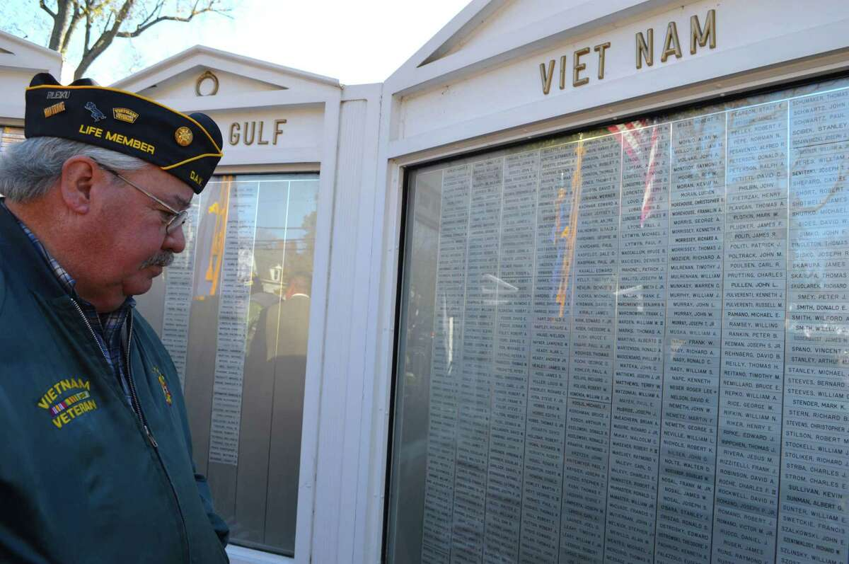 Vietnam veteran Bob Grilley, who grew up in Fairfield and now lives in Trumbull, looks over the names, including his own, on the Memorial Honor Wall at the annual Veterans Day ceremony at Town Green, Saturday, Nov. 11, 2017, in Fairfield, Conn.