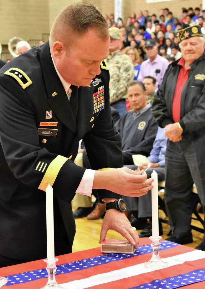 """During Needville High School's Veterans Day program on Friday, Maj. Gen. Samuel """"Lee"""" Henry, Division Commander, 36th Infantry Division, Texas Army National Guard, lights a candle in remembrance of those who paid the ultimate sacrifice for their country. Photo: Needville ISD"""