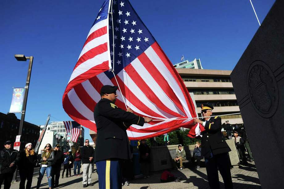 Staff Sgt. Ricardo Calderon hoists the American flag during the annual Veterans Day ceremony in Stamford. Photo: Michael Cummo / Hearst Connecticut Media / Stamford Advocate