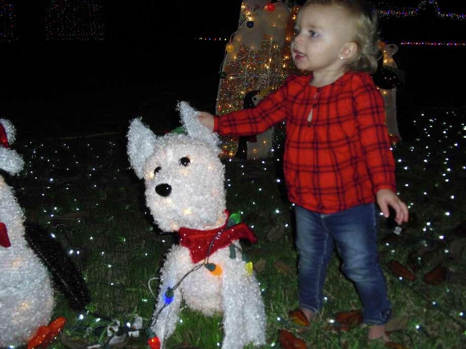 Kaleigh Murphree visits the holiday display in her front yard in Katyland. Photo: Karen Zurawski