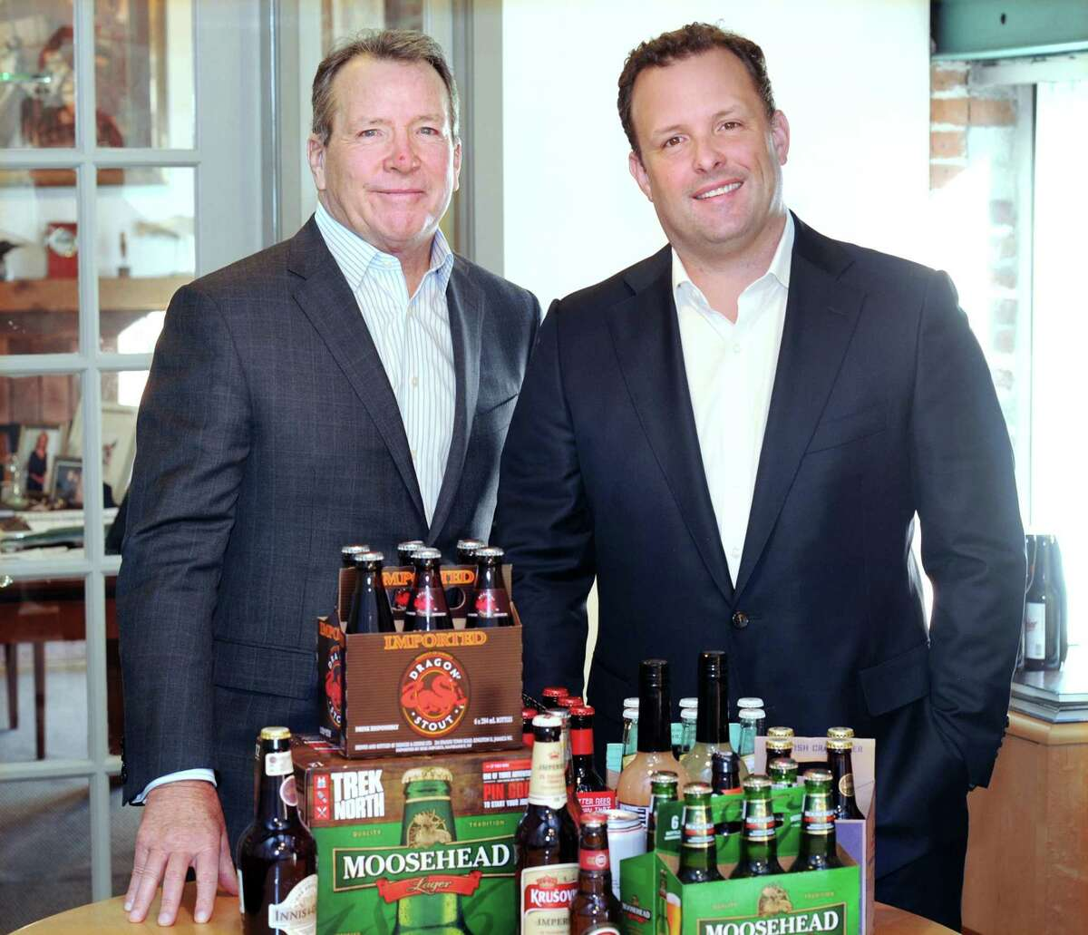 United States Beverage Chief Executive Officer Joseph Fisch, left, with his son, Justin Fisch, who was recently promoted to president of the company, posed with their company's beverages at their company headquarters in Stamford, Conn., Friday, Nov. 10, 2017. The company is entering its third decade of business competing in the U.S. beer industry and focuses on the imported and U.S. craft beer, cider and specialty beverage markets.