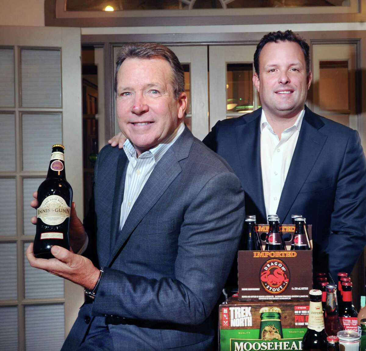 United States Beverage Chief Executive Officer Joseph Fisch, left, with his son, Justin Fisch, who was recently promoted to president of the company, posed with their company's beverages at their headquarters in Stamford, Conn., Friday, Nov. 10, 2017. The company is entering its third decade of business competing in the U.S. beer industry and focuses on the imported and U.S. craft beer, cider and specialty beverage markets.