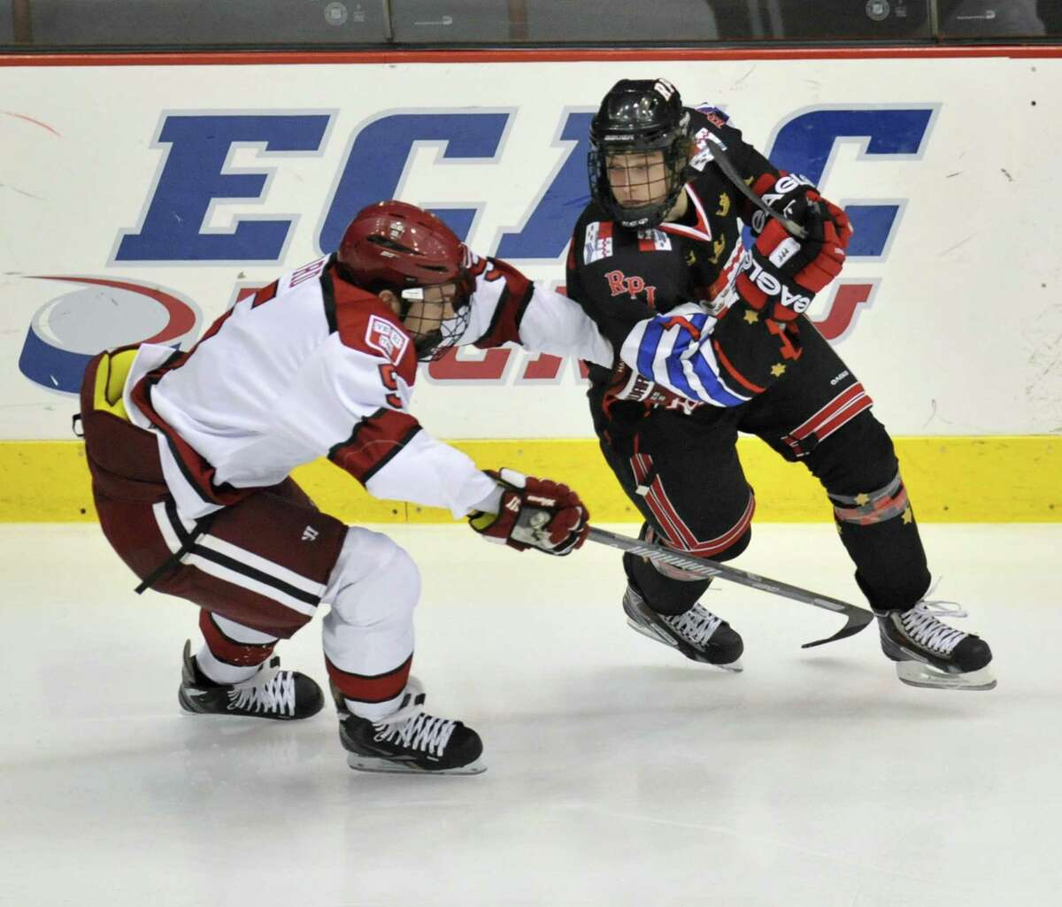 Harvard University's Dan Ford (5) and Rensselaer Polytechnic InstituteZach Schroeder (7) against chase a puck during the first period of a ECAC college hockey game in Troy N.Y., Tuesday, Oct. 29, 2013. (Hans Pennink / Special to the Times Union)