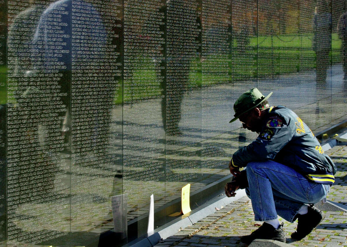 WASHINGTON, : US Marine Corps Vietnam Veteran Cpl. Mal Simpson of Philadelphia, Pennsylvania, kneels at the Vietnam Veterans Memorial 10 November 2001 to pay his respects for fallen comrades in Washington, DC. Veteran's Day is 11 November, the annual commemoration when the nation honors its war dead. AFP PHOTO/Mike THEILER (Photo credit should read MIKE THEILER/AFP/Getty Images)