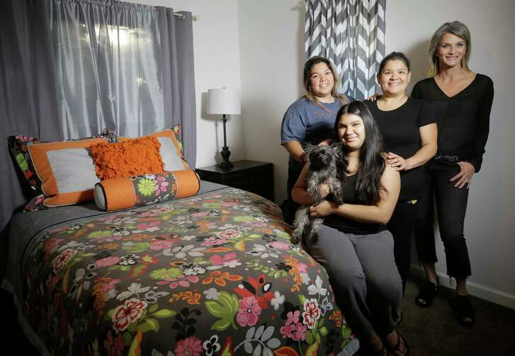 LeTricia Wilbanks, right, helped the Nietos - Wendy, from left, Ashley with her dog, Vivi, and their mother Anel - replace furniture damaged by floodwaters.