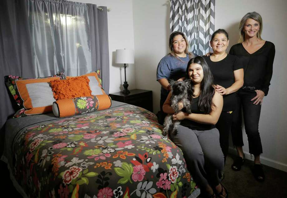 LeTricia Wilbanks, right, helped the Nietos - Wendy, from left, Ashley with her dog, Vivi, and their mother Anel - replace furniture damaged by floodwaters. Photo: Melissa Phillip, Houston Chronicle / © 2017 Houston Chronicle