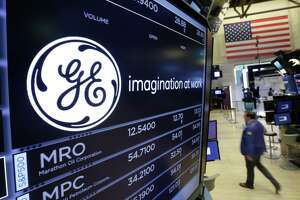 FILE - In this Monday, June 12, 2017, file photo, the General Electric logo appears above a trading post on the floor of the New York Stock Exchange. GE said Monday, Nov. 13, 2017, that it is slashing its quarterly dividend in half with investors gathering in Boston, where Chairman and CEO John Flannery is expected to lay out significant changes for the U.S. company. (AP Photo/Richard Drew, File)