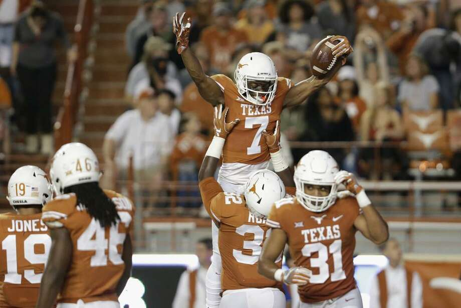Texas' Malcolm Roach, No. 32, lifts Antwuan Davis, No. 7, in celebration after an interception in the second quarter at Darrell K Royal-Texas Memorial Stadium on Nov. 11, 2017 in Austin, Texas during UT's victory over Kansas. Photo: Tim Warner /Getty Images