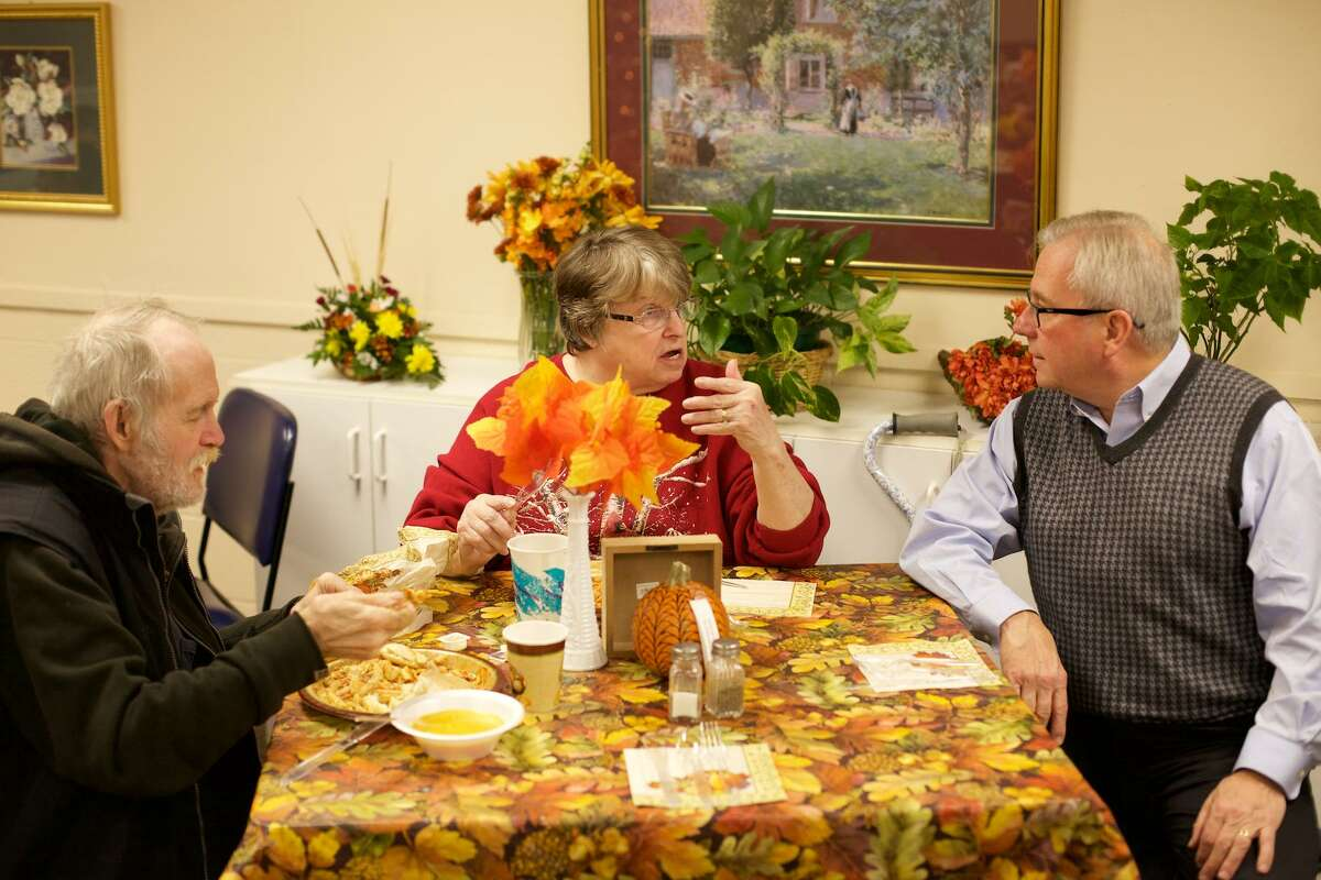 First Selectman Matt Knickerbocker chats with Susan and Kevin Johns from Bethel during a holiday dinner. The Thanksgiving meal was held in the Senior Center cafeteria in the Clifford J. Hurgin Municipal Center on Thursday, November 24, 2016, from noon to 4pm.