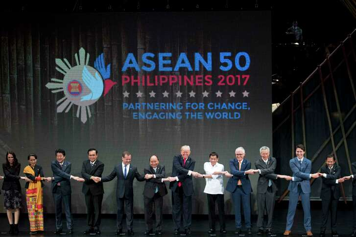 """President Donald Trump, center, and other leaders do the """"ASEAN-way handshake"""" on stage during the opening ceremony at the ASEAN Summit at the Cultural Center of the Philippines on Nov. 13, 2017, in Manila, Philippines. Trump is on a five-country trip through Asia traveling to Japan, South Korea, China, Vietnam and the Philippines. (AP Photo/Andrew Harnik)"""